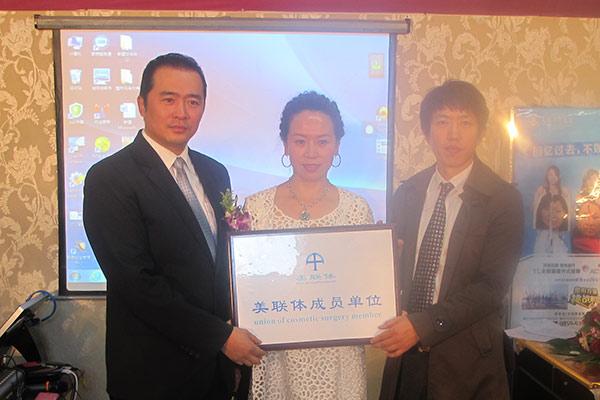 美联体胡劲松教授和何栋良秘书长为大庆天姿授予美联体合作单位牌匾